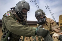 Senior Airman Tabitha Hastert, an aircrew flight equipment technician with the 514th Air Mobility Wing, Air Mobility Command, assists an air crew member with the 732nd Airlift Squadron, 514th Air Mobility Wing, through a simulated decontamination station at the Combat Readiness Training Center at Gulfport, Mississippi, March 8, 2017. Close to 700 AMC Airmen from the 514th Air Mobility Wing, 305th Air Mobility Wing, 87th Air Base Wing, and the 621st Contingency Response Wing at Joint Base McGuire-Dix-Lakehurst, N.J., are participating in the mobilization exercise Crisis Response 2017. The primary goal of this exercise is for the four wings to deploy to an austere location and set up and sustain combat air mobility operations. (U.S. Air Force photo by Master Sgt. Mark C. Olsen/Released)