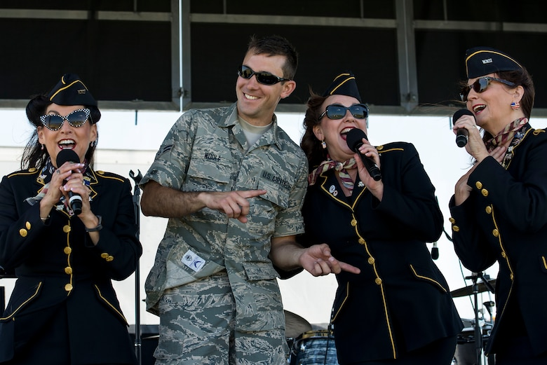 The Ladies for Liberty sing a song with Airman 1st Class Jim Woolf, Band of Mid-America audio engineer, during the Scott Airshow and Open House at Scott Air Force Base, Ill., June 11, 2017. Ladies for Liberty is a singing troupe dedicated to performing the Andrew Sisters style of music through their own rendition of vocals, costumes, hairstyles, and the spirit of patriotism reminiscent of the 1940s. (U.S. Air Force photo by Tech. Sgt. Jonathan Fowler)