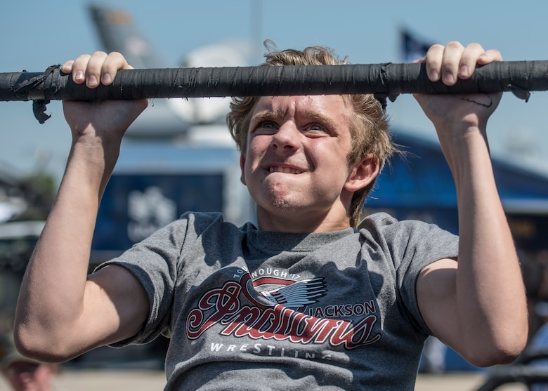"A boy attempts to complete 15 pullups at the recruiting station during the Scott Air Force Base Air Show, Scott Air Force Base, Ill., June 11, 2017. The base hosted the air show and open house to celebrate the 100th year of Scott AFB.  Over 50 aircraft, ranging from WWI's Curtiss JN-4 Jenny to the currently utilized KC-135 Stratotanker, came to Scott, the fourth oldest Air Force base. Demonstrations included the Black Daggers, ""Tora, Tora, Tora,"" and the USAF Thunderbirds. Opened in 1917 and previously named Scott Field, the base has seen its mission evolve and expand to encompass a multitude of priorities, including aeromedical evacuation and communications.  Today, Scott is home to 31 mission partners and provides around-the-clock logistics support and rapid global mobility, carried out primarily by U.S. Transportation Command and Air Mobility Command."