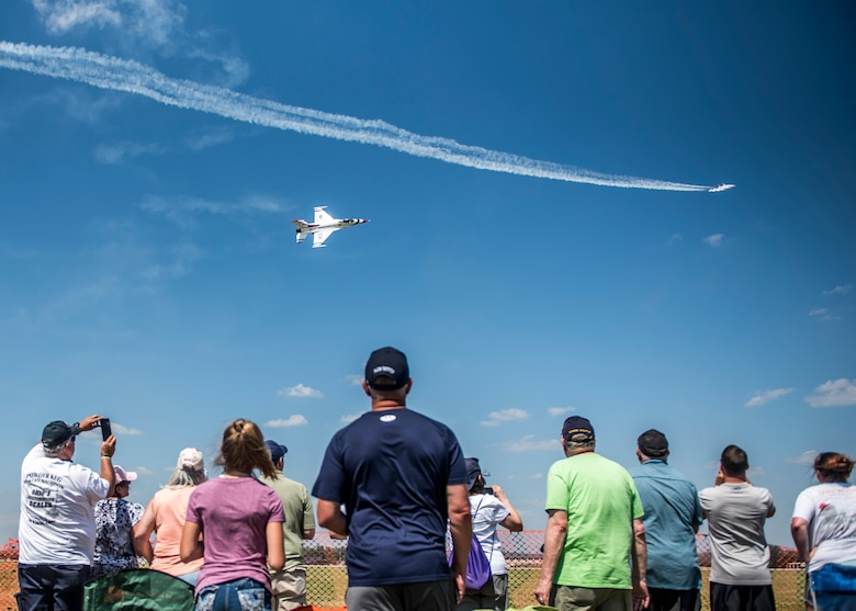 "The crowd watched the Thunderbirds performance during the Scott Air Force Base Air Show, Scott Air Force Base, Ill., June 11, 2017. The base hosted the air show and open house to celebrate the 100th year of Scott AFB.  Over 50 aircraft, ranging from WWI's Curtiss JN-4 Jenny to the currently utilized KC-135 Stratotanker, came to Scott, the fourth oldest Air Force base. Demonstrations included the Black Daggers, ""Tora, Tora, Tora,"" and the USAF Thunderbirds. Opened in 1917 and previously named Scott Field, the base has seen its mission evolve and expand to encompass a multitude of priorities, including aeromedical evacuation and communications.  Today, Scott is home to 31 mission partners and provides around-the-clock logistics support and rapid global mobility, carried out primarily by U.S. Transportation Command and Air Mobility Command."