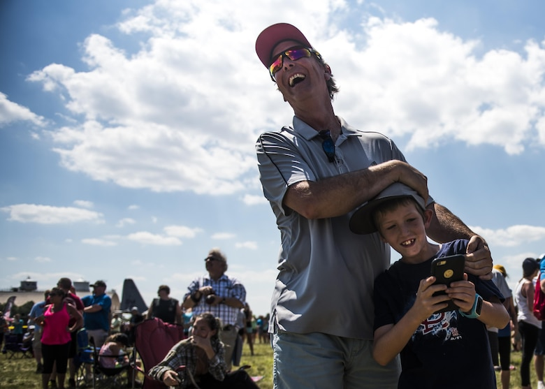 "A father embraces his son in laughter after the Thunderbirds's roar startled him during the Scott Air Force Base Air Show, Scott Air Force Base, Ill., June 11, 2017. The base hosted the air show and open house to celebrate the 100th year of Scott AFB.  Over 50 aircraft, ranging from WWI's Curtiss JN-4 Jenny to the currently utilized KC-135 Stratotanker, came to Scott, the fourth oldest Air Force base. Demonstrations included the Black Daggers, ""Tora, Tora, Tora,"" and the USAF Thunderbirds. Opened in 1917 and previously named Scott Field, the base has seen its mission evolve and expand to encompass a multitude of priorities, including aeromedical evacuation and communications.  Today, Scott is home to 31 mission partners and provides around-the-clock logistics support and rapid global mobility, carried out primarily by U.S. Transportation Command and Air Mobility Command."
