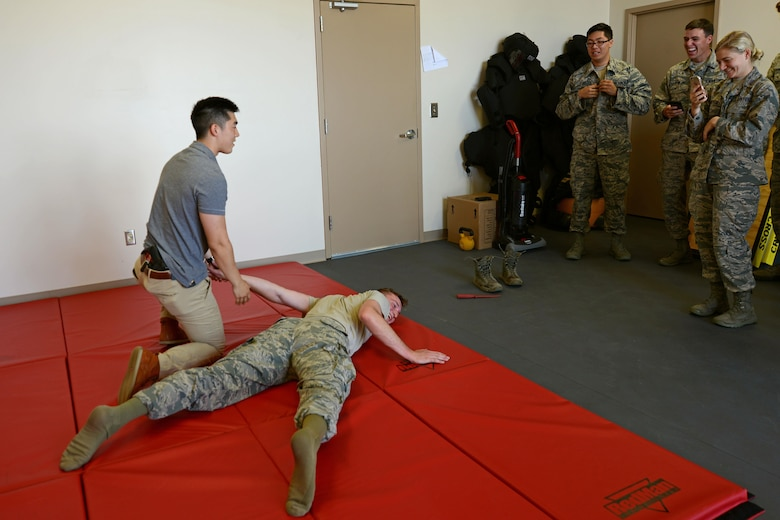 U.S. Air Force Special Agent James Min from the Office of Special Investigations Detachment 212 holds Cadet 2nd Class Parker Rosedahl, U.S. Air Force Academy cadet, on a mat at Shaw Air Force Base, S.C., June 9, 2017. Min demonstrated a take-down technique to cadets during their visit as part of the Operation Air Force program. (U.S. Air Force Airman 1st Class Kathryn R.C. Reaves)