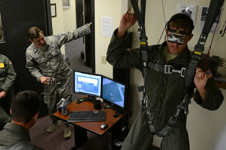 U.S. Air Force Cadet 2nd Class Michael Triner, U.S. Air Force Academy cadet, hangs in a harness while others watch a display at Shaw Air Force Base, S.C., June 12, 2017. Triner and other cadets participated in hanging harness training using a virtual reality headset to learn how to safely navigate a parachute during their visit as part of the Operation Air Force program. (U.S. Air Force Airman 1st Class Kathryn R.C. Reaves)