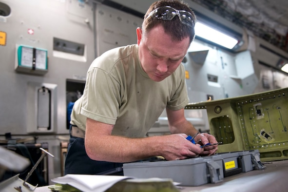 Tech. Sgt. Anthony Scolaro, an aircraft structural maintenance technician, references technical specifications as he looks for a tool while completing a repair on a jack support box for a C-17 Globemaster III aircraft, May 15, at the 167th Airlift Wing.(U.S. Air National Guard photo by Senior Master Sgt. Emily Beightol-Deyerle)