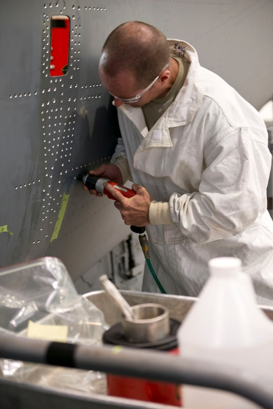 Staff Sgt. Doug Miller plugs a hole on the exterior of a C-17 Globemaster III aircraft, May 23, 2017. The hole is plugged with aluminum using a cryogenic process where the aluminum shrinks during the freezing process and then expands once it is installed. The 167th maintainers installed a new jack support box, typically done at Air Force depot facilities, over a three week period at the wing.(U.S. Air National Guard phtoo by Senior Master Sgt. Emily Beightol-Deyerle)