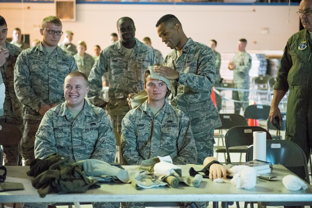 Capt. Jumaane Green (far right), a Chaplin at the 167th Airlift Wing in Martinsburg, W.Va., wraps the head of Airman 1st Class Daniel Frantz (middle), a member of the 167th, while Airman 1st Class Shawn Mcmahon (left) waits his turn during Self Aide Buddy Care (SABC) training, June 9, 2017. A training rodeo, set up by base training, members were able to complete the required Self Aide Buddy Care (SABC), Law of Armed Conflict and Chemical Biological Radiological and Explosive training. (U.S. Air National Guard photo by Staff Sgt. Jodie Witmer)