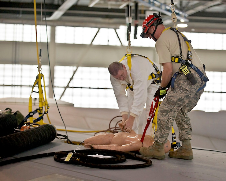 """Tech. Sgt. James Cline, a 167th aircraft fuel systems mechanic and Tech. Sgt.Milo Zahnow, a 167th fire fighter and, rescue a """"victim"""" during a confined space emergency extraction exercise, June 9, at 167th Airlift Wing, Martinsburg, W.Va. The exercise simulated a person losing consciousness inside one of the four fuel tanks aboard a C-17 Globemaster III. (U.S. Air National Guard photo by Tech. Sgt. Michael Dickson)"""