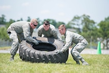 Members of security forces at the 167th Airlift Wing in Martinsburg, W.Va., Airman 1st Class Jamie Bryner (left), Airman 1st Class Jalen Newcome (middle), and Airman 1st Class Cody Kunkleman (right), lift a tire during an expeditionary fitness challenge with both strength and stamina events, June 10, 2017. The course consisted of seven stations, where teams of five, moved as a unit from location to location and were scored by station and overall time. (U.S. Air National Guard photo by Staff Sgt. Jodie Witmer)