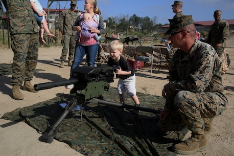 A child learns how to use a Mark 19 grenade launcher during the 9th Communication Battalion's family day, April 28, 2017, at Camp Pendleton, Calif. The event was for spouses and children to meet Marines and experience what their loved ones do on a daily basis. (U.S. Marine Corps photo by Lance Cpl. Robert Alejandre)