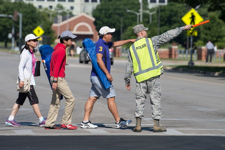 A volunteer directs traffic during the Centennial Celebration Air Show, June 11, 2017, Scott Air Force Base, Ill. Scott AFB opened in 1917, previously named Scott Field, the base has seen its mission evolve and expand to encompass a multitude of priorities, including aeromedical evacuation and communications. (U.S. Air Force photo by Senior Airman Melissa Estevez)