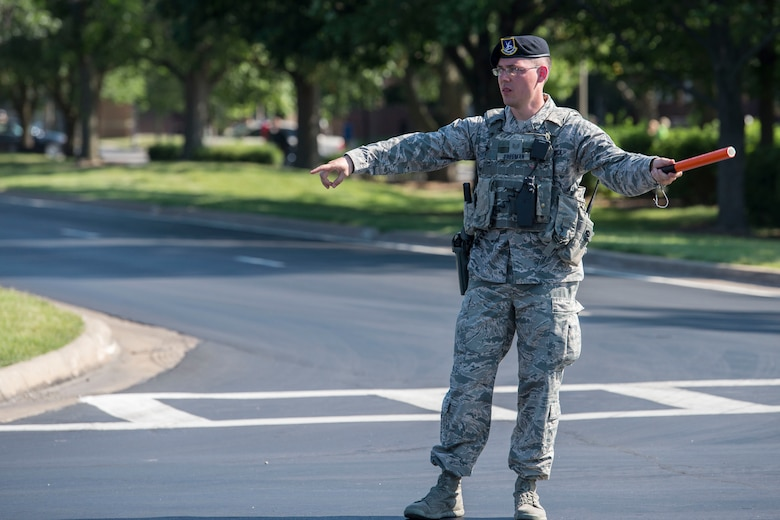 A security forces member directs traffic during the Centennial Celebration Air Show, June 11, 2017, Scott Air Force Base, Ill. Scott AFB opened in 1917, previously named Scott Field, the base has seen its mission evolve and expand to encompass a multitude of priorities, including aeromedical evacuation and communications. (U.S. Air Force photo by Senior Airman Melissa Estevez)