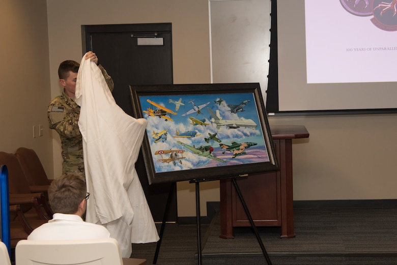 A painting containing all the aircraft the squadron has flown during its history is revealed during the 33rd Special Operations Squadron 100-year ceremony at Cannon Air Force Base, June 9, 2017. The squadron has roots dating back to 1917 during World War I and since then has had a presence in nearly every major U.S. conflict. (U.S. Air Force photo by Staff Sgt. Michael Washburn/Released)