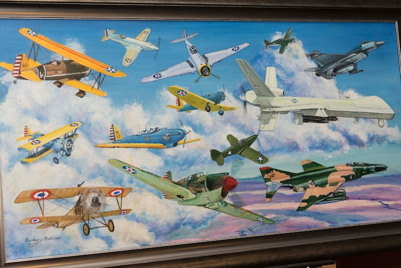 A painting depicting the aircraft used during the 33rd Special Operations Squadron's 100-year history is revealed during the 33rd SOS 100-year ceremony at Cannon Air Force Base, New Mexico, June 9, 2017. The painting was done by Rodney Bohner, father of Lt. Col. Ryan Bohner, 33rd SOS commander. (U.S. Air Force photo by Staff Sgt. Michael Washburn/Released)