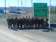 Staff at Canadian Armed Forces Forward Operating Location Inuvik pose for a picture with Marines from with Engineer Company, Detachment Bravo, Marine Wing Support Squadron 473, 4th Marine Aircraft Wing, Marine Forces Reserve at the entrance to FOL Inuvik, May 31, 2017. The Marines completed engineering projects at FOL Inuvik to increase force protection measures at FOL Inuvik during their two-week annual training period, May 26 to June 9, 2017.