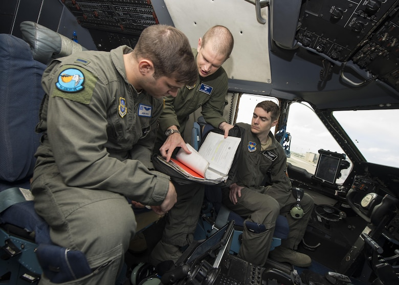 Maj. Brandon Stock, C-5M Formal Training Unit commander, instructs pilot students, 1st Lt. Jason Feys and 1st Lt. Sam Haueter, during preflight procedures June 8, 2017, inside a C-5M Super Galaxy flight deck on Dover Air Force Base, Del. Feys and Haueter are undergoing C-5M initial pilot qualification training. (U.S. Air Force photo by Senior Airman Zachary Cacicia)