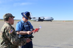 Alaska National Guard Sgt. Elijah Gutierrez, a civil operator with the Counterdrug Support Program, discusses the procedures for using the Narcan kit with Alaska State Trooper James Lester at the Edward G. Pitka Sr. Airport in Galena, Alaska, May 31, 2017. Twelve Guardsmen from the CDSP traveled to the Yukon-Koyukuk Region hub to deliver the kits that block the effects of opioids and reverses an overdose, and to provide drug and alcohol education and prevention materials to local residents. (U.S. Army National Guard photo by Staff Sgt. Balinda O'Neal Dresel)