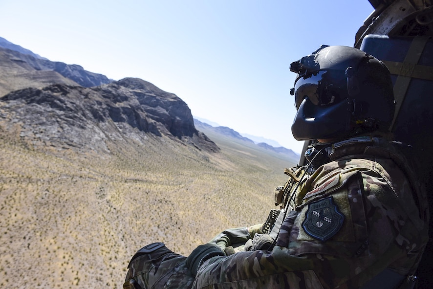 Staff Sgt. Christian Nault, 34th Weapons Squadron special mission aviator, searches the area for the landing zone during a Weapons School Integration mission at the Nevada Test and Training Range June 1, 2017. The HH-60 crew successfully performed a combat search and rescue mission during the exercise. (U.S. Air Force photo by Airman 1st Class Andrew D. Sarver/Released)