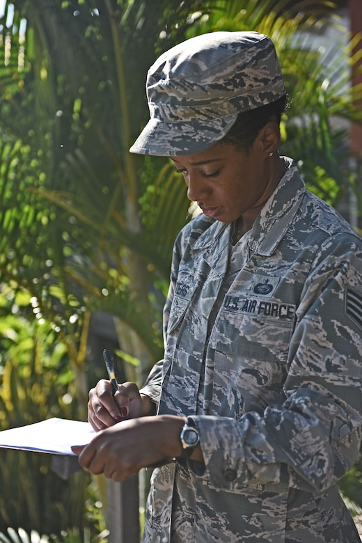 Staff Sgt. Jenerian Walters, Joint Task Force-Bravo personnel office, checks the passenger list for the Soto Cano shuttle bus that will transport deployed personnel to the airport for their return home after completing an assignment at JTF-Bravo. Staff Sgt. Walters Call to Duty as the Admin non-commissioned officer at JTF-Bravo begins at 7:45 am as she waits for shuttle bus passengers at the bus stop.