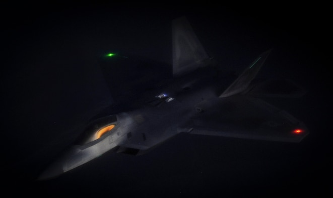 An F-22 Raptor fighter jet, assigned to the 433rd Weapons Squadron at Nellis Air Force Base, Nev., maneuvers after being refueled by a KC-135 Stratotanker during a Weapons School Integration mission over the Nevada Test and Training Range June 8, 2012. One of the most important planned aspects of this mission is holding it during the hours of darkness. (U.S. Air Force photo by Senior Airman Kevin Tanenbaum/Released)