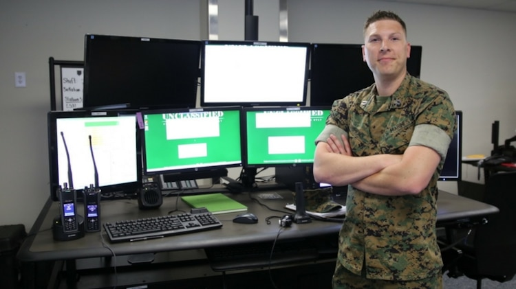 Maj. Mark Simmons, systems engineer for Consolidated Emergency Response System, stands in front of a newly-installed CERS emergency dispatcher workstation aboard Marine Corps Base Quantico, Va.  CERS aggregates multiple capabilities—Enhanced 911, Computer-Aided Dispatch, and fire station alerting—into a single workstation, giving emergency dispatchers the ability to quickly dispatch the appropriate assets where necessary. CERS increases the effectiveness of emergency response operations aboard Marine Corps installations worldwide. (U.S. Marine Corps photo by Ashley Calingo)