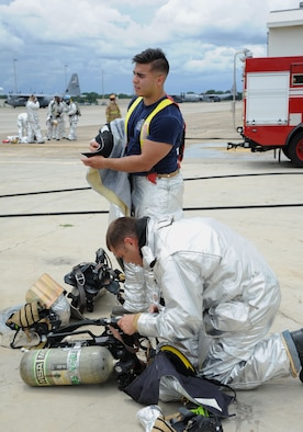 Staff Sgt. Daniel Braitman and Senior Airman Jonathan Martinez, 81st Infrastructure Division firefighters, gear up during a live fire exercise on the flightline June 6, 2017, on Keesler Air Force Base, Miss. The Keesler Fire Department, the Gulfport CRTC Fire Department and the Stennis Space Center Fire Department are all required to practice Aircraft Rescue and Fire Fighting procedures to meet a semi-annual training requirement. (U.S. Air Force photo by Kemberly Groue)
