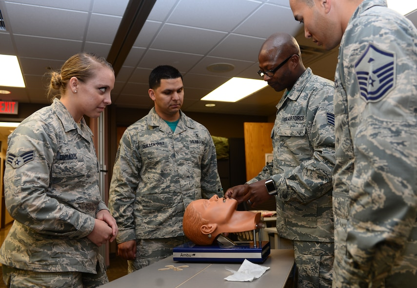 Master Sgt. Nathan Landry, the first sergeant assigned to the 28th Medical Group, and Master Sgt. Luis Guillen-Diaz, the mental health flight chief and additional-duty first sergeant assigned to the 28th MDG, join Staff Sgt. Ricky Dunbar, an education and training noncommissioned officer in charge assigned to the 28th MDG, while he teaches a course on CPR at Ellsworth Air Force Base, S.D., June 9, 2017. Each first sergeant has a handful of additional-duty first sergeants, usually around four or five, ready to drop what they're doing at moment's notice to take up the mantel. (U.S. Air Force photo by Airman 1st Class Donald C. Knechtel)