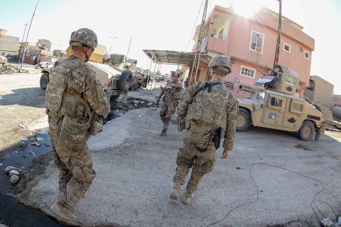 U.S. and Iraqi army Soldiers greet each other in a neighborhood liberated from ISIS in Mosul, Iraq, June 8, 2017. The U.S. Army Soldiers, deployed in support of Combined Joint Task Force - Operation Inherent Resolve and assigned to 2nd Brigade Combat Team, 82nd Airborne Division, enable their ISF partners through the advise and assist mission, contributing planning, intelligence collection and analysis, force protection, and precision fires to achieve the military defeat of ISIS. CJTF-OIR is the global Coalition to defeat ISIS in Iraq and Syria. (U.S. Army photo by Staff Sgt. Jason Hull)