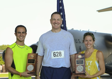 Col. Robert Lyman, Joint Base Charleston commander, center, congratulates Clay Askew, Space and Naval Warfare Systems Command civilian contractor, left, and U.S. Navy Lt. Katherine Wirtz, Naval Nuclear Power Training Command instructor, right, for being the first male and female to cross the finish line at Joint Base Charleston's 9th annual Run the Runway here, June 10. Two hundred and seventy nine runners consisting of military members, their families and civilians participated in the run alongside 100 volunteers. (U.S. Air Force photo/Senior Airman Thomas T. Charlton)