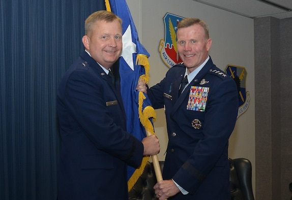 """On June 8, Brig. Gen. James R. """"Cliffy"""" Cluff, vice commander, 25th Air Force, accepts his general officer flag from Gen. Tod D. Wolters, commander, U.S. Air Forces in Europe, U.S. Air Forces Africa and Allied Air Command; and director, Joint Air Power Competence Centre, after his promotion. Cluff is responsible to the 25th Air Force commander for providing multisource Intelligence, Surveillance and Reconnaissance products, applications, capabilities and resources; electronic warfare; and integrating cyber ISR forces and expertise."""