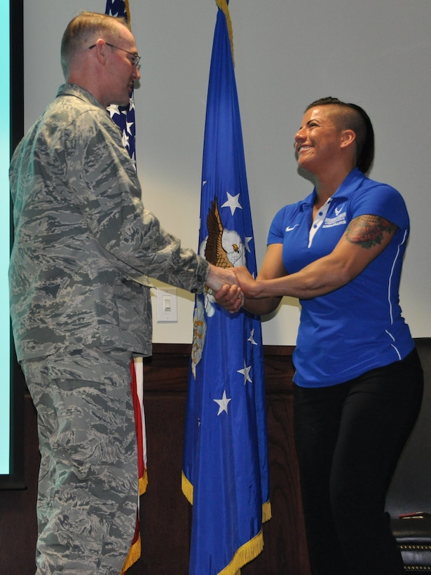 Col. Roger Suro, 340 Flying Training Group Commander, coins retired Staff Sgt. Sebastiana Lopez-Arellano after she shared her story of  resilience and recovery at the unit's spring MUTA on June 8 at Joint Base San Antonio-Randolph, Texas. Lopez-Arellano  lost her right leg in a 2015 motorcycle crash. She went on to compete and medal several times at the Air Force Warrior Games and Invictus. (Photo by Janis El Shabazz, 340 FTG Public Affairs).