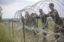 COLD LAKE, AB, CANADA – Combat Engineer Marines with Marine Wing Support Squadron 473, 4th Marine Aircraft Wing, Marine Forces Reserve, place a length of concertina wire to construct a triple standard concertina fence around their forward arming and refueling point at Canadian Forces Base Cold Lake during exercise Maple Flag 50, June 1, 2017. MWSS-473 is providing real world refueling support to Royal Canadian Air Force CH-147 Chinook and CH-146 Griffon type model series during exercise Maple Flag 50. (U.S. Marine Corps photo by Lance Cpl. Niles Lee/Released)