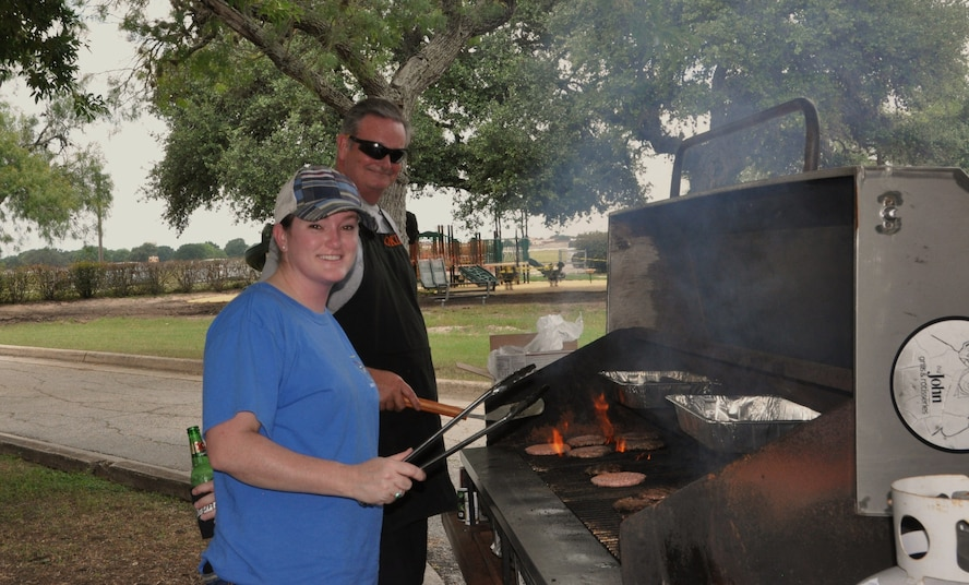 Master Sgt.Sarah Cornelius and Larry Tutor, 340 Flying Training Group Director of Staff, grill up burgers and brats during the Group picnic held after the Group's spring MUTA at Joint Base San Antonio, Texas, June 8-9. (Photo by Janis El Shabazz, 340 FTG, Public Affairs)
