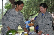 Master Sgt. Tainell Pettengill (L) and Master Sgt. Vianca Contreras sample goodies at the 340 Flying Training Group's picnic after the unit's spring MUTA held at Joint Base San Antonio, Texas, June 8-9.. (Photo by Janis El Shabazz, 340 FTG Public Affairs)