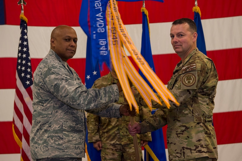 Maj. Gen. Anthony Cotton, 20th Air Force and Task Force 214 commander, passes the guidon to Col. Joshua Bowman, 582nd Helicopter Group commander, during the 582nd HG change-of-command ceremony at F.E. Warren Air Force Base, Wyo., June 13, 2017. The ceremony signified the transition of command from Col. David Smith. (U.S. Air Force photo by Staff Sgt. Christopher Ruano)