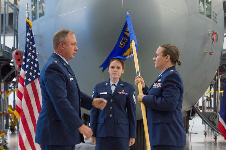 U.S. Air Force Col. Pete Linde, 153rd Maintenance Group commander, passes the 153rd Aircraft Maintenance Squadron guidon to Maj. Elizabeth Evans during an assumption of command ceremony June 10, 2017 in Cheyenne, Wyoming. Evans previously held the position of 153rd Maintenance Operations Flight commander.
