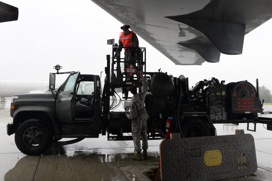 U.S. Air Force Airman 1st Class Lorenzo Jackson, a 354th Logistics Readiness Squadron fuels distribution operator, passes a bonding wire up to a TDY Airman to refuel a KC-135 Stratotanker during RED FLAG-Alaska (RF-A) 17-2 June 12, 2017, at Eielson Air Force Base, Alaska. The fuels Airmen are busy day and night during RF-A exercises to fuel all participating aircraft. (U.S. Air Force photo by Airman 1st Class Cassandra Whitman)