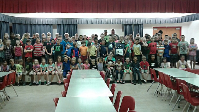 U.S. Air Force Master Sgt. Anthony Molina, 97th Maintenance Directorate inspection managements flight chief, and students from Duke Elementary School pose for a photo, May 17, 2017, at Duke Elementary School, Oklahoma. The students of Duke Elementary received a U.S. flag that had been flowing during combat operations overseas as thanks for writing deployed members during the holidays. (Courtesy Photo/Released).