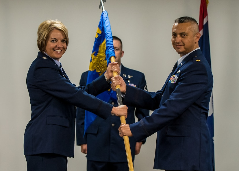 U.S. Air Force Lt. Col. Michelle Mulberry, 153rd Mission Support Group commander, passes the 153rd Civil Engineering Squadron guidon to Maj. Gabriel Herrera, during a change of command ceremony, June 11, 2017 in Cheyenne, Wyoming. Herrera assumes command from Lt. Col. Bret Trippel. (U.S. Air National Guard photo by Tech. Sgt. John Galvin)