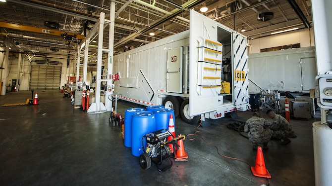 The 91 Maintenance Group power, refrigeration, electrical, laboratory Global Strike Challenge team works behind a payload transport trailer at Minot Air Force Base, N.D., May 31, 2017. The three-member PREL team is responsible for the inspection and maintenance of the payload transport trailer's electrical systems and environmental climate control. (U.S. Air Force photo/Senior Airman J.T. Armstrong)