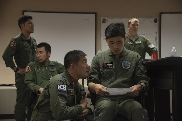 Republic of Korea Air Force (ROKAF) Capt. Yeo Myeonghwan, center left, the 20th Tactical Fighter Wing (TFW) escort flight leader out of Seosan Air Base, Korea, speaks with Capt. Lee Min Kyu, center right, a 20th TFW pilot, about their roles in the mission during RED FLAG-Alaska 17-2, June 12, 2017, at Eielson Air Force Base, Alaska. ROKAF's role included playing as an escort for bombers during training. (U.S. Air Force photo by Airman 1st Class Sadie Colbert)