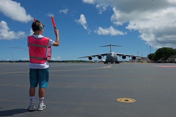 Luke Dillon, son of U.S. Air Force Maj. Gen. Mark Dillon, Pacific Air Forces vice commander, helps marshal a C-17 Globemaster III that his father flew on for his fini flight at Joint Base Pearl Harbor-Hickam, Hawaii, June 12, 2017. With Dillon's retirement approaching, the fini-flight is the capstone event in his flying career. Moments after his arrival, Dillon was greeted by family and friends and soaked in water and champagne to celebrate his Air Force career. (U.S. Air Force photo/Tech. Sgt. Kamaile Chan)