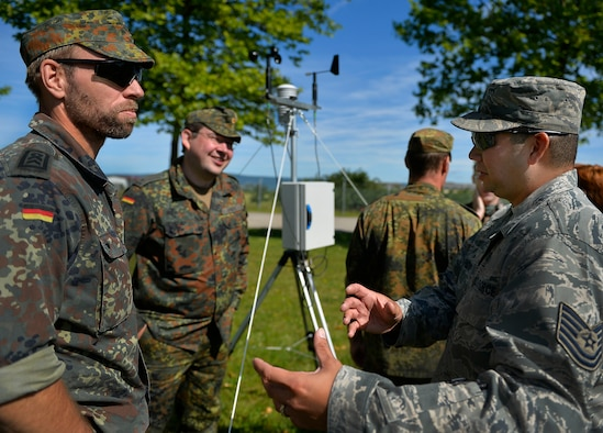 U.S. Air Force Tech. Sgt. Christopher Hardy, 7th Weather Squadron noncommissioned officer  in charge of regional weather maintenance, right, speaks with German NATO partners during a weather-related exercise in Wiesbaden, Germany, June 12, 2017. The 7th WS uses Exercise Cadre Focus to enhance its capability to provide weather support to U.S. Army operations in Europe. (Air Force photo by Airman 1st Class Joshua Magbanua)