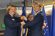 Col. Carolyn Stickell (right) relinquishes her command of the Headquarters Individual Reservist Readiness and Integration Organization, June 12. Stickell passed the HQ RIO guidon to Brig. Gen. Ellen Moore, the Headquarters Air Reserve Personnel Center Commander, who presided over the ceremony and later presented the guidon to the new HQ RIO commander, Col. Kelli B. Smiley.