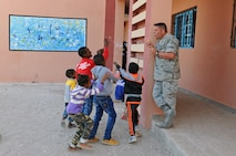 Staff Sgt. Erik Bornemeier, a medical technician with the 151st Medical Group, entertains a group of children waiting outside of the clinic in Issafen, Morocco on April 25, 2017 during African Lion. (U.S. Air National Guard photo by Tech. Sgt. Annie Edwards)