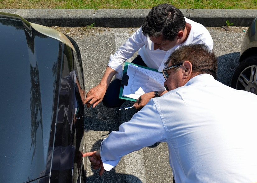 Stefano Marazzi and Giampiero Lauro, contracted driving instructors, evaluate tire wear as part of a vehicle inspection, June 13, 2017 at Aviano Air Base, Italy. Eleven different safety items were checked during the vehicle inspection before a hands-on driving test. (U.S. Air Force photo by Senior Airman Cary Smith)