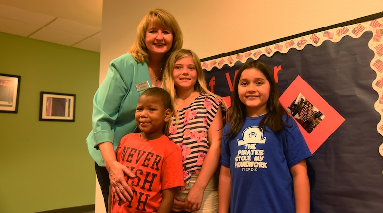 Vicki Rygiel, 21st Force Support Squadron School Age Care program coordinator, smiles with Christian Smithwick, Coady Sellers and Emma Mosley, SAC program children, inside the R.P. Lee Youth Center at Peterson Air Force Base, Colorado, Monday, June 12, 2017. Rygiel earned the Air Force Civilian Specialist of the Year award in recognition of her service with Schriever's SAC program. (U.S. Air Force photo/Airman 1st Class William Tracy)