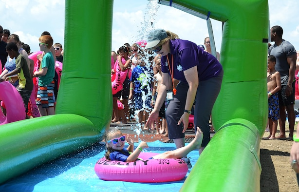 Vicki Rygiel, former Schriever School Age Care program coordinator, gives Zoey Boone a push down the giant slip-and-slide during Slide the City at Schriever Air Force Base, Colorado, Aug. 19, 2016. During her more than three years at Schriever, Rygiel participated in and organized many events to help kids learn and have fun on base, earning her Air Force level recognition. (U.S. Air Force photo/Brian Hagberg)