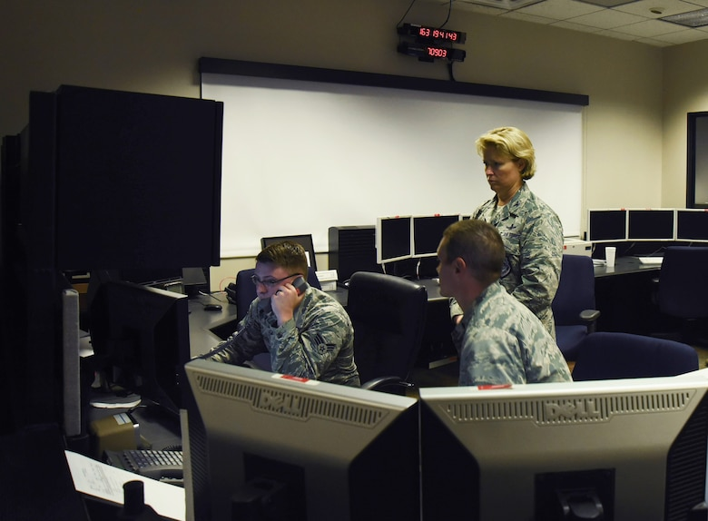 Col. DeAnna Burt, 50th Space Wing Commander, prepares to give the final command to decommission satellite 32 to Senior Airman Brandon Myers, 2nd Space Operations Squadron satellite system operator, at Schriever Air Force Base, Colorado, Monday, June 12, 2017. The disposal process began on June 5 with the spin-stabilized configuration. (U.S. Air Force photo/Airman 1st Class William Tracy)