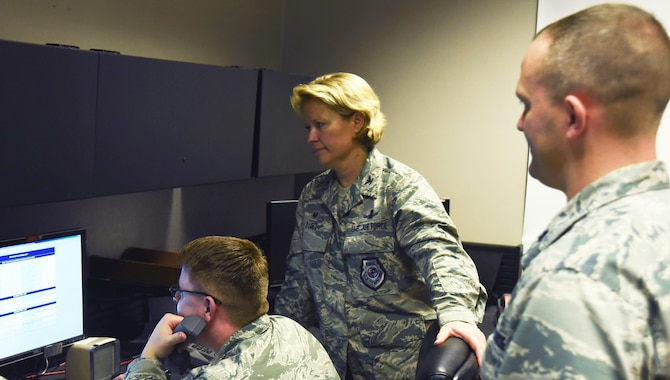 Col. DeAnna Burt, 50th Space Wing Commander, gives Senior Airman Brandon Myers, 2 SOPS satellite system operator, the final command to decommission satellite vehicle number 32 at Schriever Air Force Base, Colorado, Monday, June 12, 2017. First Lt. Col. Peter Norsky, 2 SOPS commander, observes the final command.  (U.S. Air Force photo/Airman 1st Class William Tracy)