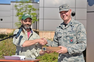 Andy Schlosberg, a Colorado State Forester, presents a Tree City USA plaque to Lt. Col. Andrew DeRosa, 50th Civil Engineer Squadron commander, at the Child Development Center at Schriever Air Force Base, Colorado, Friday, June 9, 2017.  The presentation was made on Arbor Day in honor of Schriever's 19th year as a Tree City USA recipient. (U.S. Air Force Photo/Dennis Rogers)